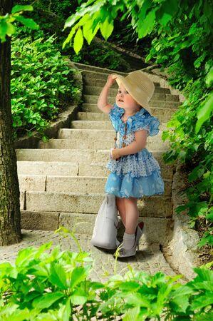 petite fille avec robe: Mode-semeur. Jeune fille en robe bleue avec un sac et un chapeau Banque d'images