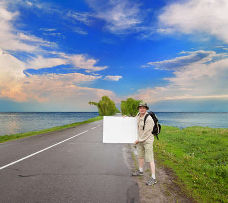brisk: brisk tourist with a poster on a relief picturesque clouds are over the ocean