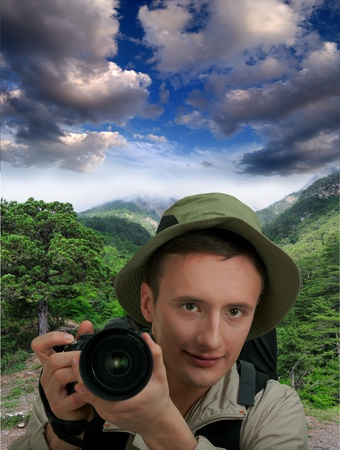 young man tourist with camera on white photo