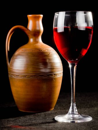 potation: Pitcher and a glass of red liquid on a black background