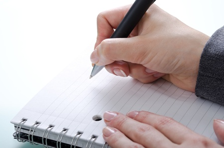 signatory: womans hand with a pen on a notebook