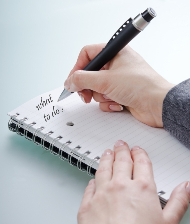 womans hand with a pen on a notebook