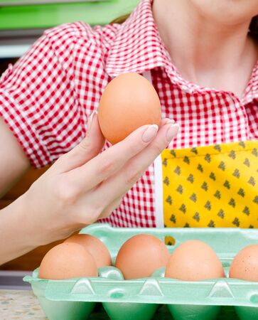 housewife chooses eggs on the background of kitchen interiors photo