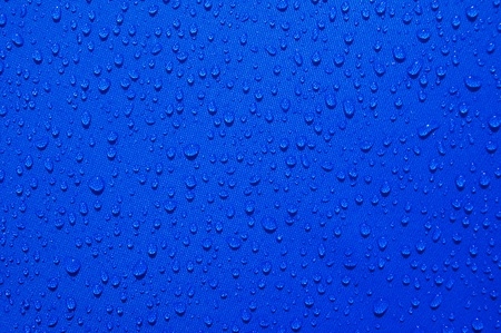 drops of clear liquid on the blue fabric photo