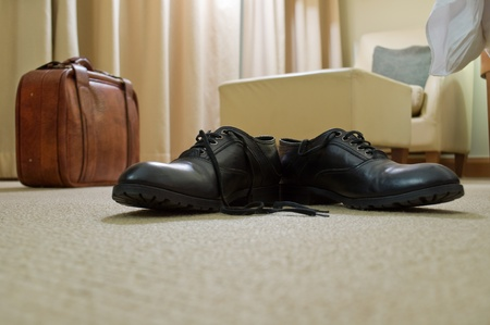 mens shoes, a suitcase in a hotel room interior diffuse photo