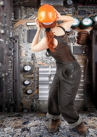 hardware repair: portrait of red haired girl in overalls on background of old electronic circuit boards