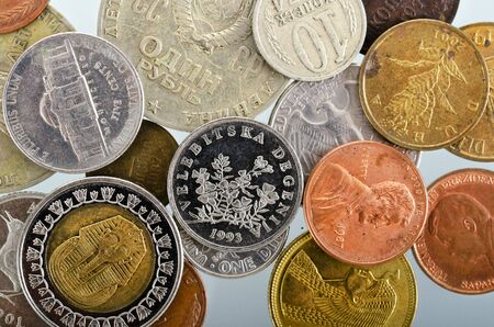 numismatics: small coins of different countries and years as a background