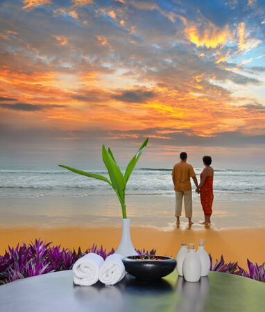 Still Life with towels, a vase with bamboo sprout and bottles and couple on the beach at sunset photo