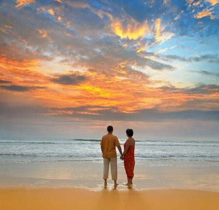 coucher de soleil: couple d'adultes sur bord de l'oc�an au coucher du soleil