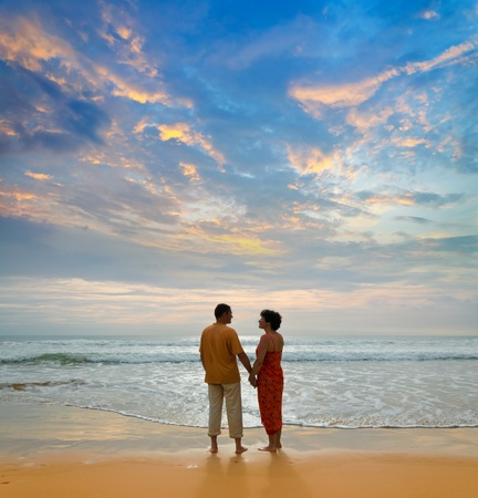 couple of adults on ocean shore at sunset photo