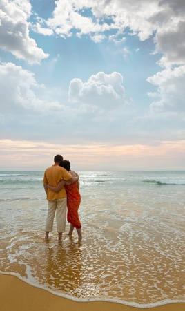 couple of adults on ocean shore at sunset
