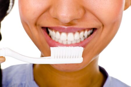 dark-skinned woman holding a toothbrush. Focus on the brush  photo