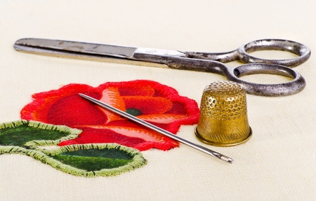 old scissors, a thimble and a needle lying on needlework  The image collected from five shots to increase the zone of focus Stock Photo - 12565599