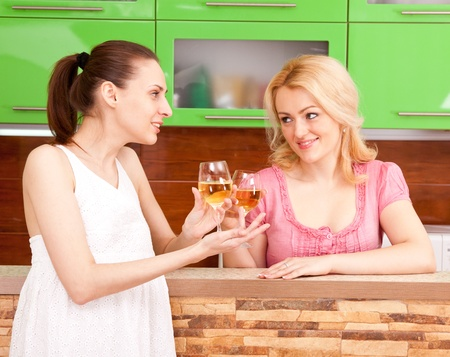 Two young women with glasses of wine in the kitchen photo