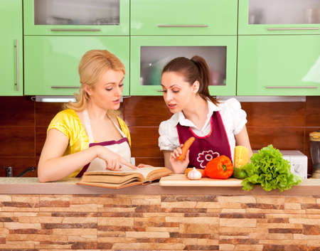 two young housewives are preparing a salad of fresh vegetables and fruits photo