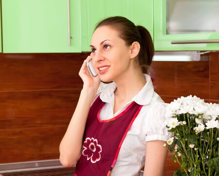 young housewife talking on the smartphone against the kitchen photo