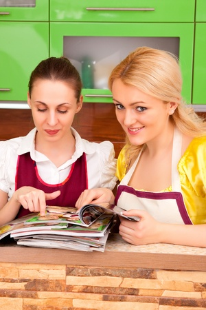 Two young women discuss fashion magazines in the kitchen photo