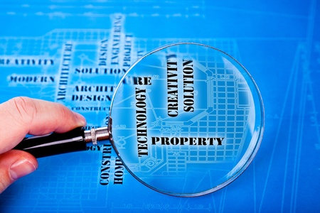 human hand with a magnifying glass on the art architectural background photo