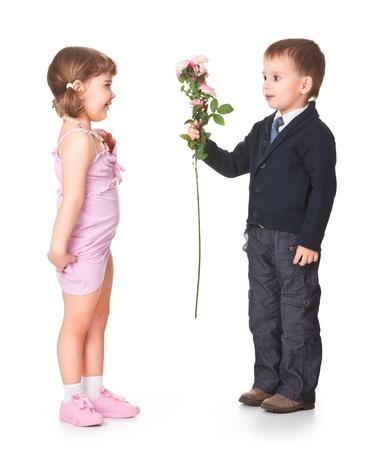 kleinen Jungen gibt Freundin Blumen, hinter einem weißen Hintergrund
