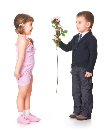 petit garçon donne des fleurs amie, derrière un fond blanc
