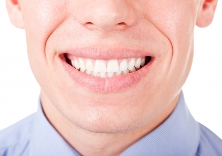 young man shows his teeth in a smile photo