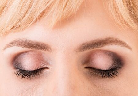 Women's closed eyes closeup coated with makeup and eyelashes glued photo