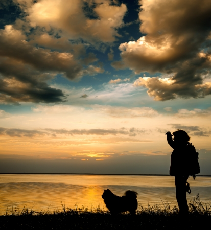 woman - tourist with a dog on the shore of beautiful Lake photo