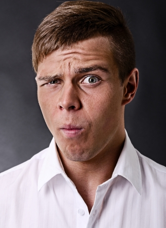 inconvenience: Portrait of a surprised and incredulous man on a black background Stock Photo