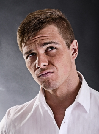displeased: Portrait of a surprised and incredulous man on a black background Stock Photo