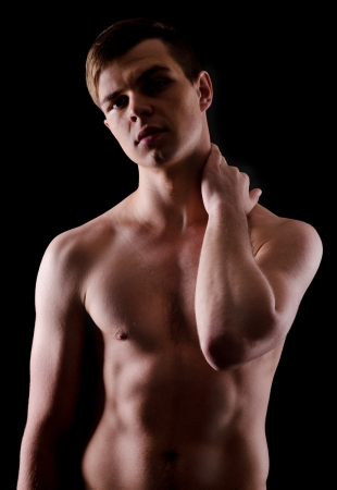 the figure of a young nude man, backlit on a black background photo