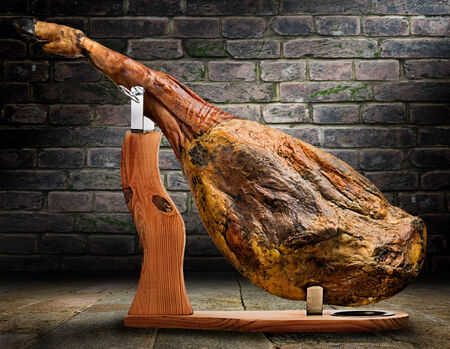 mapped: A front leg of Serrano ham mapped on a wooden stand on artistic background