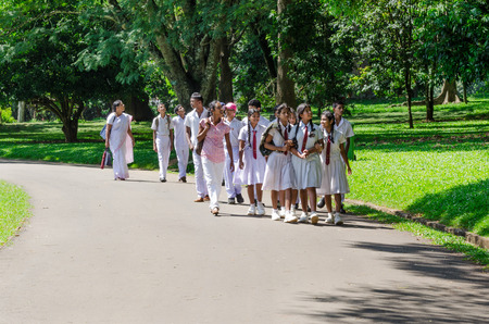 KANDY, SRI LANKA - DEC 08  A group of schoolkids in a traditional school clothes on excursion in the Royal Botanical Garden, Kandy, Sri Lanka , Dec 08, 2011