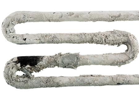 limescale: damaged electric heater . Isolation on a white background and folding of several images with different focus
