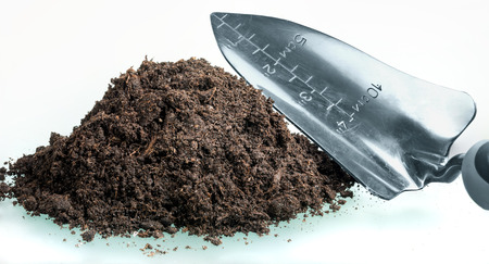Heap of compost with a garden trowel photo
