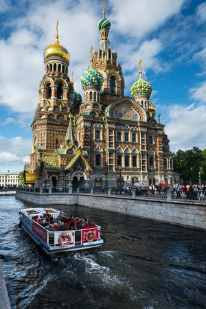 ST. PETERSBURG, RUSSIA - JULY 11, 2016: walking boat moves through the channel Griboyedov on the background Church of the Savior on Blood, St. Petersburg, Russia