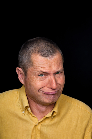 Portrait of a Man with grotesque emotions on a black background photo