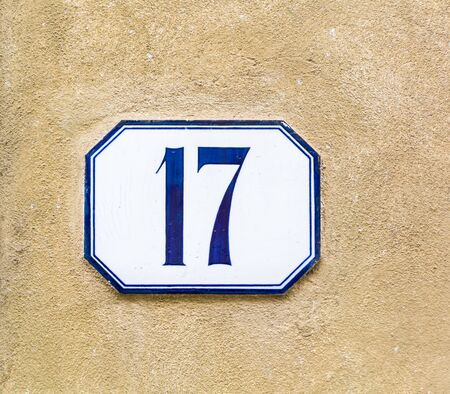 house number seventeen ( 17 ) on a roughcast wall Banco de Imagens