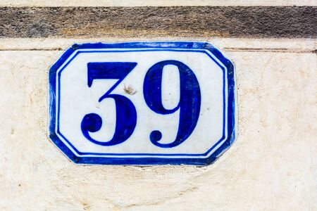 house number thirty nine ( 39 ) on a roughcast wall