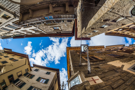 FLORENCE, ITALY - MAY 12, 2019: View up among buildings at a narrow intersection in Florence Editorial