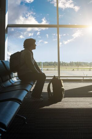 Silhouette of a tourist in an airport lounge Standard-Bild - 138047677