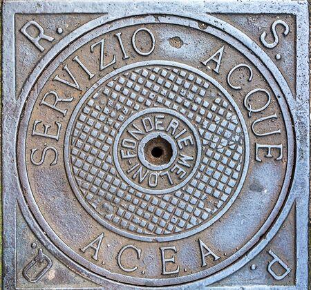 Rome, Italy - Oct 02, 2018: Old shabby manhole in Rome