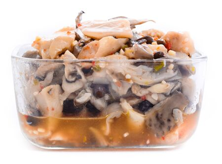 Pickled oyster mushrooms with spices in a glass bowl