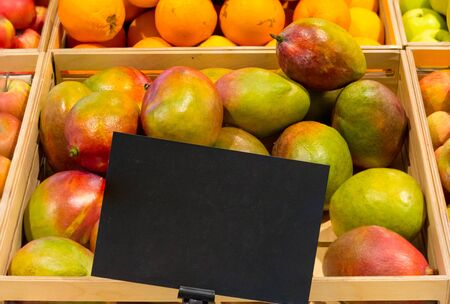 fresh mango fruit with a price tag on the counter