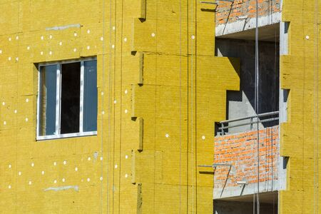 High-altitude work on the external walls of glass wool insulation and plaster Stock Photo