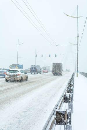KYIV, UKRAINE - NOVEMBER 29, 2016: The transport movement at the Moscow bridge during a snow storm. Kiev, Ukraine