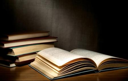 Een stapel oude boeken op de tafel.