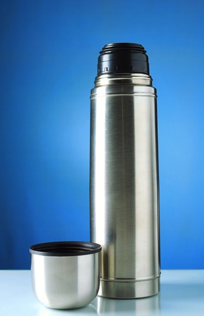 thermos mug on the table and, on a blue background photo