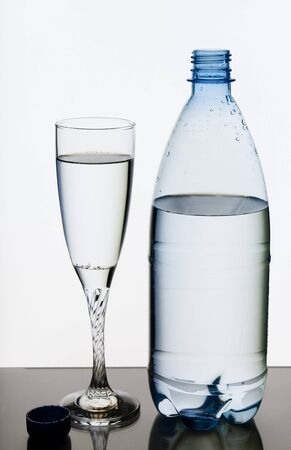 Mineral water in glass and plastic bottle photo