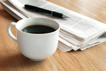 A cup of coffee and a newspaper on the table photo