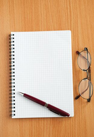 Notebook, glasses and pen on the table. photo